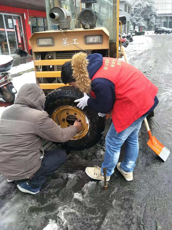 迎战冰雪丨铲雪车轮胎坏了 志愿者帮忙更换轮胎